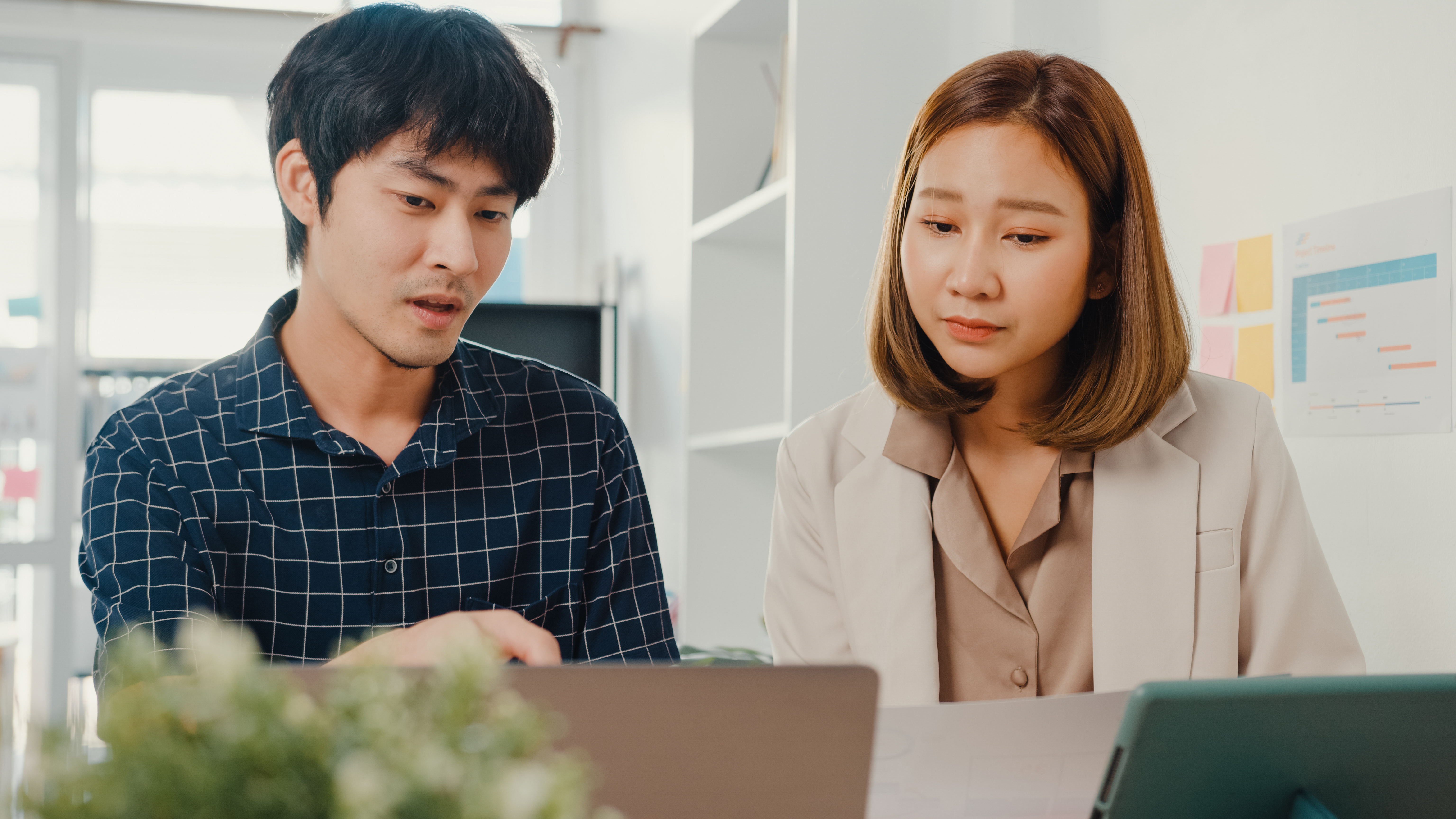 young-asian-creative-businessman-businesswoman-manager-discuss-project-compare-point-paperwork-laptop.jpg